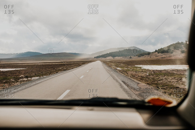 Asphalt road going through plains and hills in front of vehicle on gray overcast day in morocco