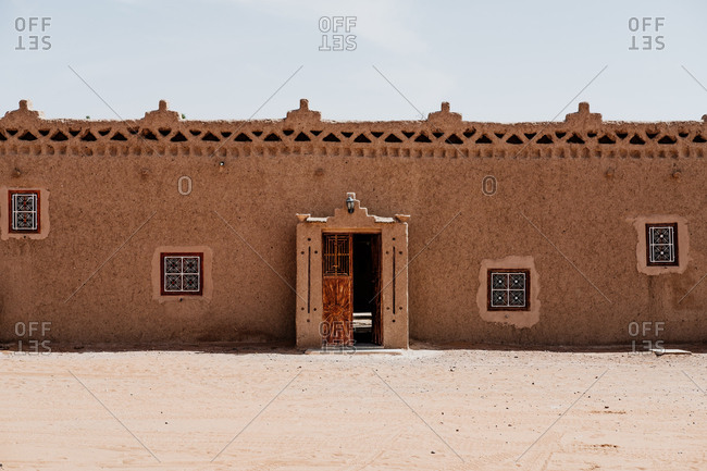 Exterior of shabby traditional arab buildings with ornaments located on street of small town against cloudless sky in morocco