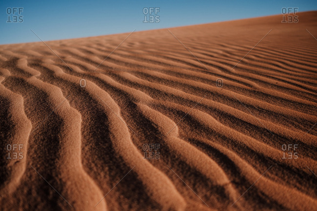 Closeup rippled sand surface on dune in arid desert against cloudless blue sky in morocco