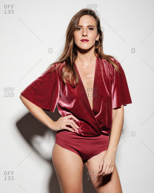 Confident young beautiful slim female model in elegant red body suit looking at camera while standing in studio on white background