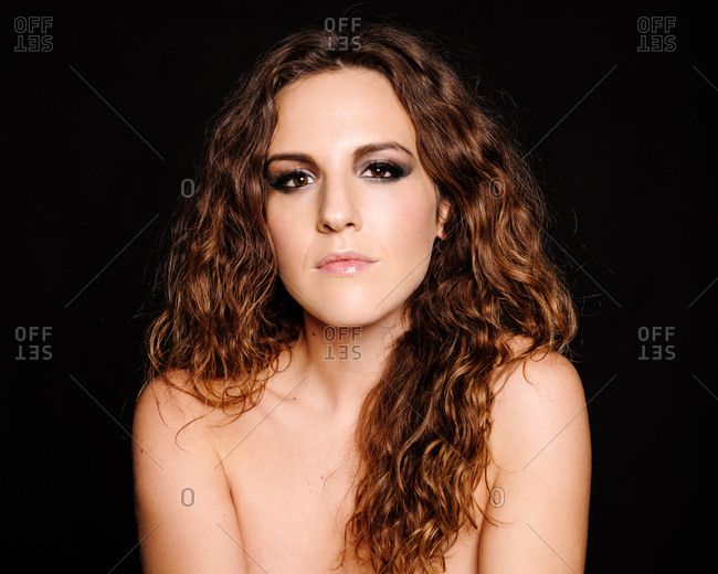 Portrait of calm brunette with curly hair and dark makeup looking at camera in studio on black background