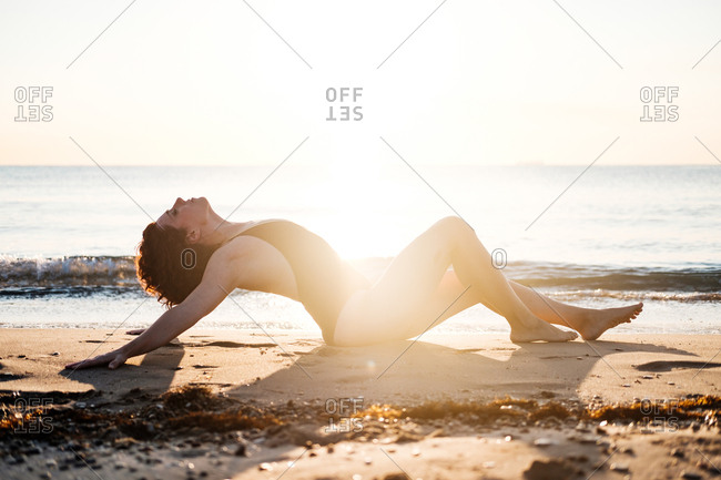 Side view of barefoot female in swimwear leaning back and closing eyes while sitting on wet sand near waving sea in back lit