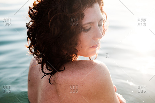 Side view of beautiful lady looking down over shoulder while standing in clean sea water on sunny day