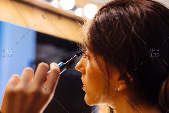 Side view of crop brunette attractive woman looking in mirror doing makeup applying mascara on eyelashes
