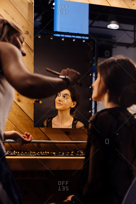 Back view of stylist applying makeup on brunette model sitting in front of illuminated mirror in dressing room