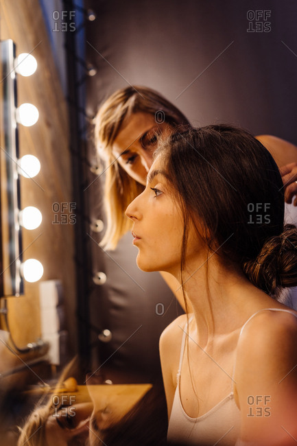 Side view of stylist applying makeup on brunette model sitting in front of illuminated mirror in dressing room
