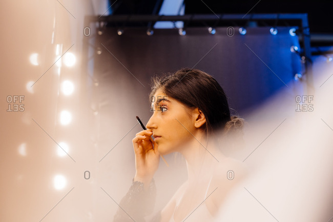 Side view of attractive woman with dark hair in black transparent dress doing makeup while sitting in front of illuminated mirror