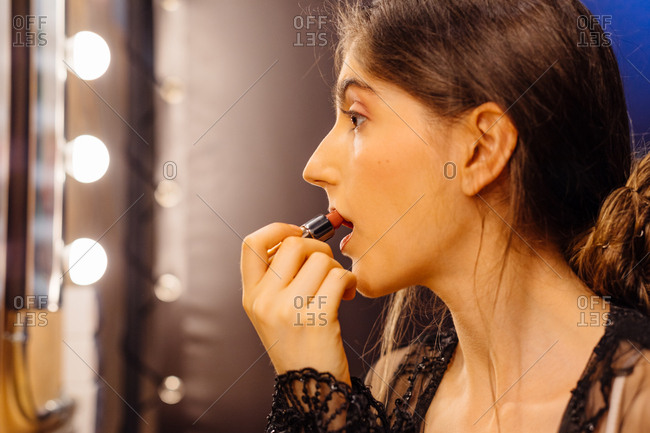 Side view of serious brunette woman in lace black dress applying red lipstick while doing makeup in dressing room