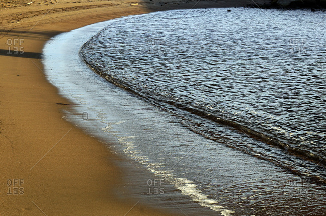Wet sandy shore on sunny day in beach