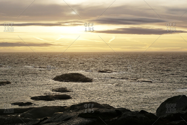 Smooth boulders on empty coast with sea waves under dark evening sky in norway