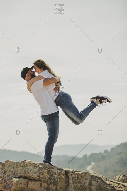 Loving couple embracing while standing at mountain cliff