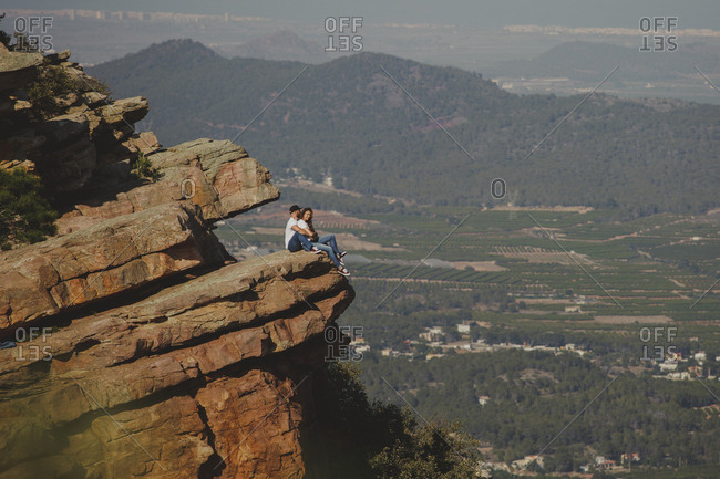 Side view of romantic relaxed couple in matching outfit hugging while sitting on edge of huge rocky mountain