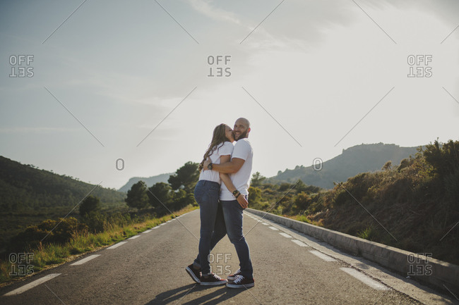 Affectionate couple hugging while standing on rural road
