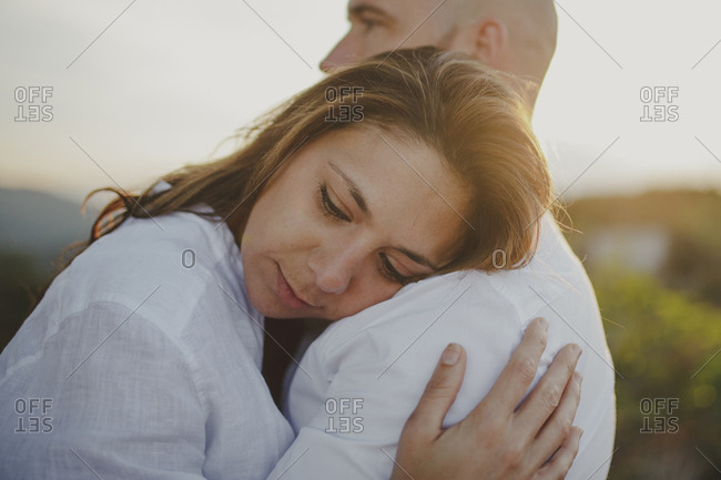 Side view of caring loving couple in matching white shirts embracing with trust while standing at grassy field at sunset