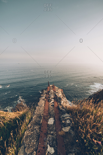 Empty stony cliff with rustic metal aged pier above dry vegetation above endless sea and twilight sky