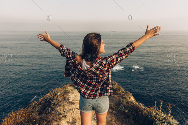 Back view of woman raising arms while standing on stony cliff against endless sea and grey sky