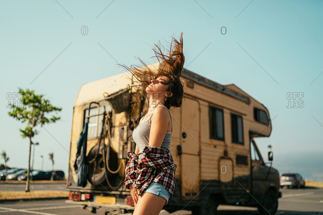Stylish attractive woman in plaid shirt and denim shorts shirt against wind on parking lot on background of camper car