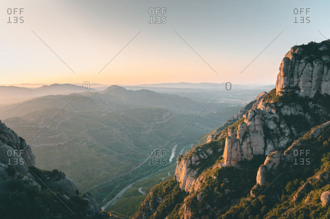 Picturesque landscape with high rocks and winding roads between green forests in sunny morning