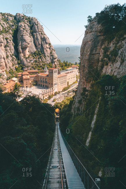 Suspension bridge leading to old brick town surrounded by high rocks green forest and sea on sunny day