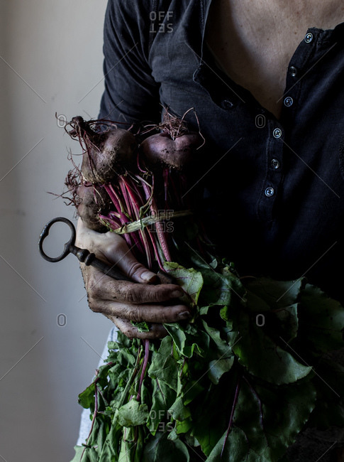 Faceless person with bunch of beetroots and key