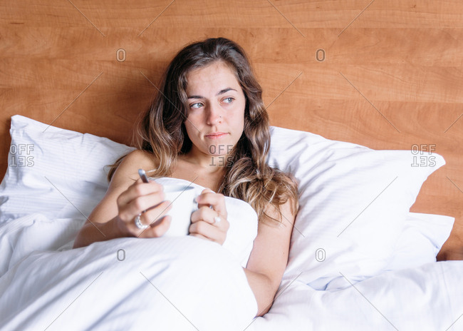 Smiling blonde girl holding a cup of coffee on a bed in the morning looking away