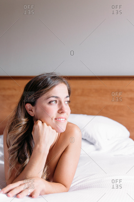 Blond girl smiling on a bed with white sheets lit by the window light in the morning