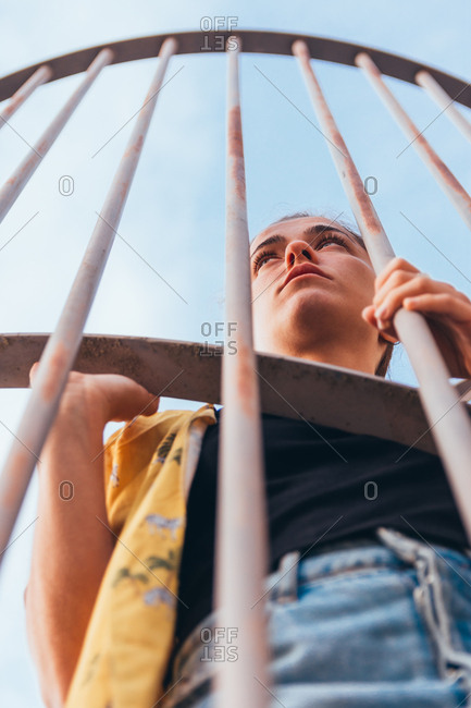 From below sensual casual woman standing in cage on clear sky in summer and looking away