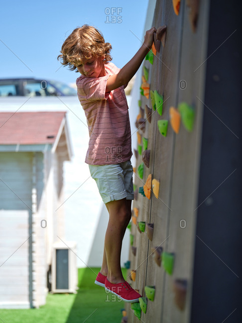 Side view of kid in casual outfit climbing wall and looking down while playing in suburban yard on sunny day
