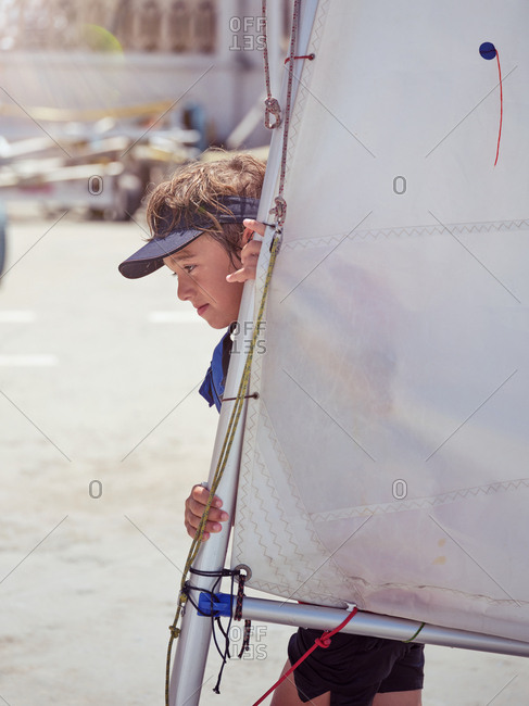 Side view of strong powerful boy walking to pier with white sail