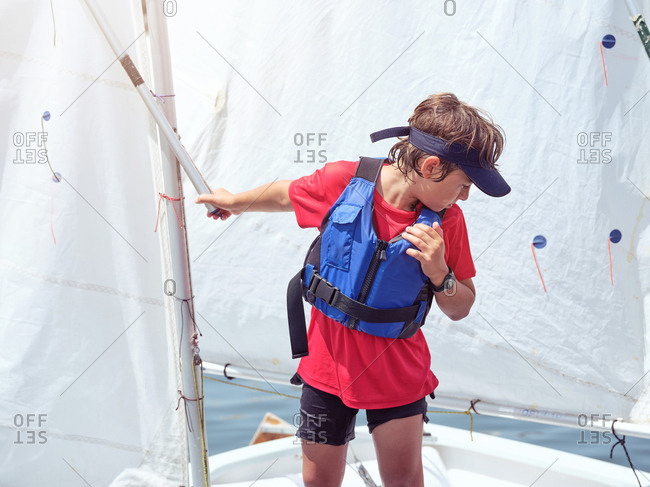 Boy in blue life jacket on yacht going to swim