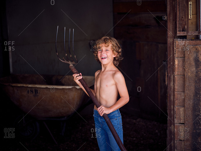 Serious shirtless boy with pitchfork standing on stall wall on farm and looking at camera