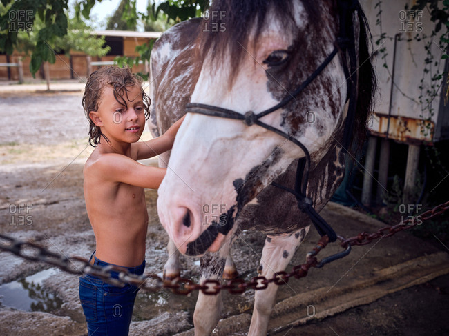Happy shirtless kid with curly wet hair embracing horse side on ranch