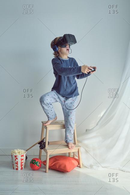 Cheerful kid in blue pajama wearing vr glasses while enjoying virtual games at home