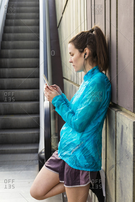 Portrait of beautiful sportswoman holding cell phone