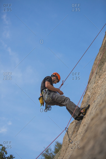 From below man climbing a rock in nature with climbing equipment