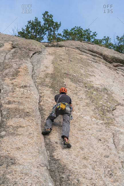 From below anonymous man climbing a rock in nature with climbing equipment