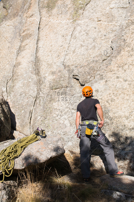A young caucasian rock climber with orange helmet is staring at the top of the mountain he is going to climb