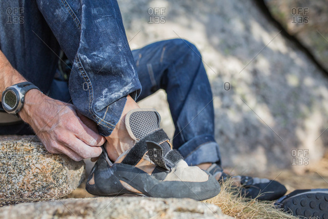 Crop unrecognizable rock climber putting on his climbers shoes to start climbing
