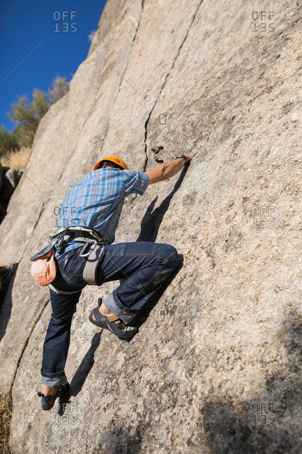 From below of unrecognizable free climber climbing in nature