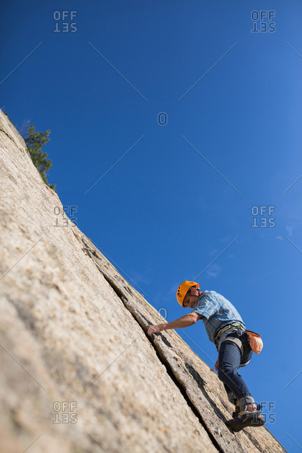 From below of free climber climbing in nature