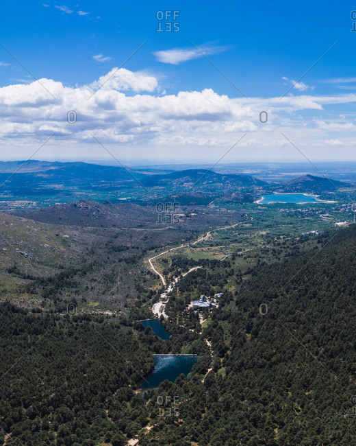 Drone view of right landscape of blue cloudy sky and lakes surrounded by forests and mountains