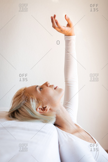 Side view of beautiful blond lady looking up and leaning on comfortable mattress against white wall at home