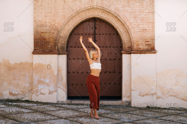 Attractive young woman in stylish outfit dancing with closing eyes against ancient building with shabby gate on street of old town