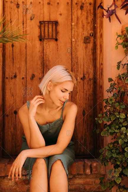 Pretty young woman with closed eyes sitting near wooden door and plants in yard
