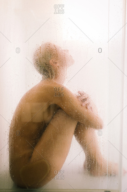Side view of young female taking shower behind wet transparent partition in bathroom