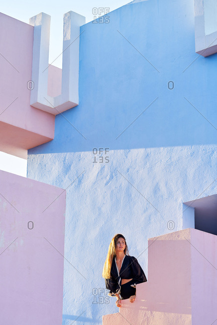Woman standing on modern blue and pink pastel building and looking away
