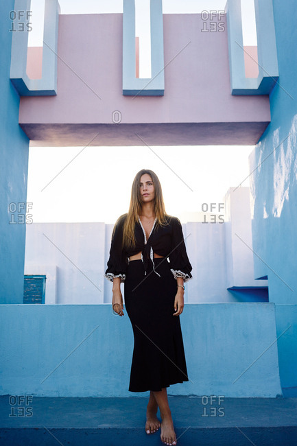 Woman standing on modern blue building and looking away