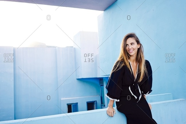 Beautiful woman leaning on modern blue wall building and looking away