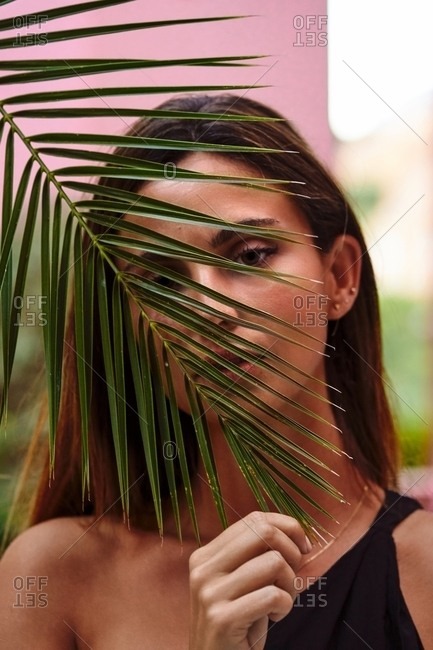 Close up of a beautiful woman looking at camera hiding face with palm tree leave