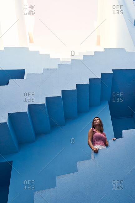 Side view of woman walking upstairs on modern blue building looking away